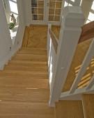 Lukket trappe med egetrin og håndliste i valnød